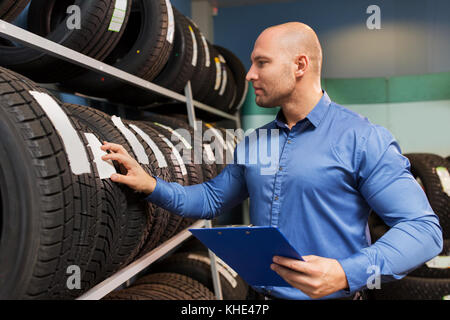 auto business owner and wheel tires at car service - Stock Photo