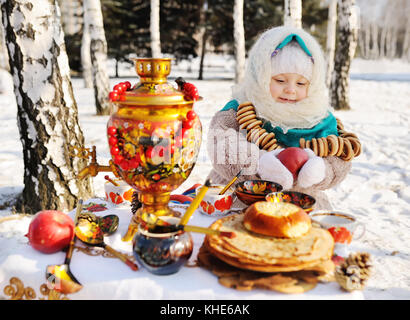 baby girl in coat and headscarf in the Russian samovar in the ba - Stock Photo