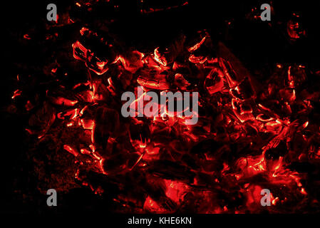 Black and red abstract background of smoldering and burning coals in the fire on a black background - Stock Photo