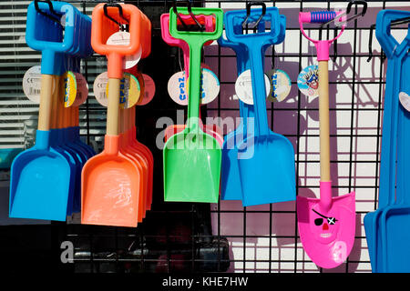 Brightly coloured plastic toy spades hanging on display outside a shop in Lyme Regis in Dorset. - Stock Photo