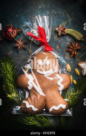 Gingerbread Man Cookie wrapped in Cellophane Bag and tied with Festive Ribbon on vintage background with fir branches - Stock Photo