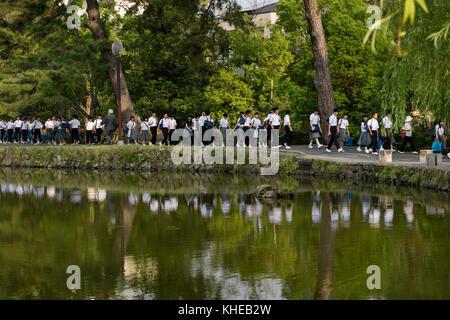 Nara, Japan -  May 30, 2017: Groups of Japanese students walking along the Sarusawa-ike, Sarusawa pond in Nara on - Stock Photo