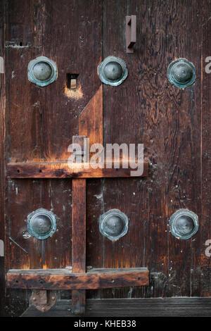 Nara, Japan - May 31, 2017: Ancient wooden door with bronze ornaments at the Kofukuji Temple - Stock Photo