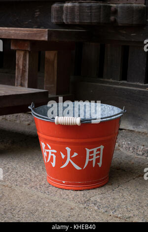 Nara, Japan -  May 31, 2017: Traditional red fire bucket with water in front of the wooden temple as fire prevention