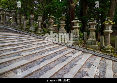 Nara - Japan, May 31, 2017: Row of many stone lanterns that lead up to the Kasuga Taisha shrine - Stock Photo