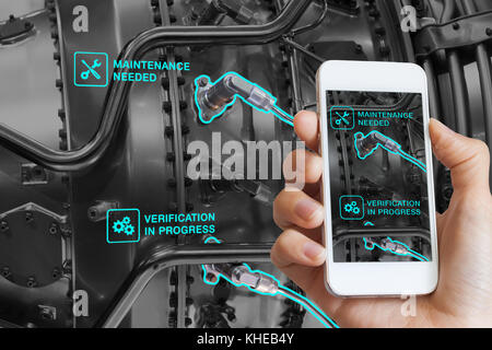 Augmented Reality technology maintenance and service of mechanical parts, technician using smartphone with AR interface - Stock Photo