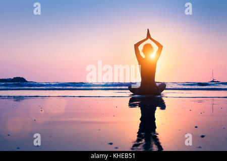 Silhouette of young woman practicing yoga, lotus position, and meditating on the beach - Stock Photo