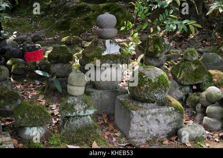 Iga Ueno - Japan, June 1, 2017:  Piled up stones symbolizing Jizo covered with moss in Ueno park - Stock Photo
