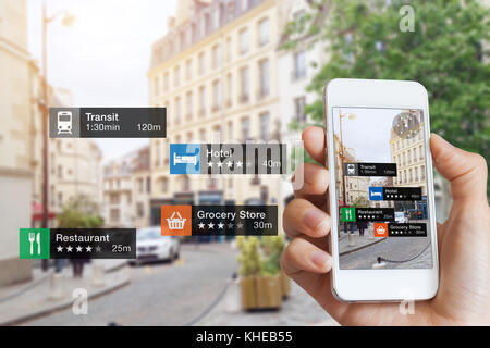 Augmented Reality (AR) information technology about nearby businesses and services on smartphone screen guide customer - Stock Photo