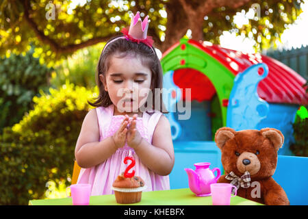 Baby toddler girl in outdoor second birthday party clapping hands at cake with Teddy Bear as best friend, playhouse - Stock Photo