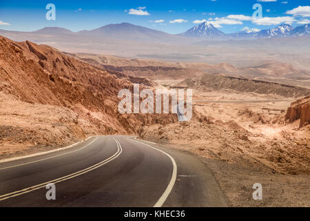 Road leading through the arid landscape at the Valley of the Moon in Chile - Stock Photo