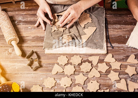 Close-up, two female potters make a lot of Christmas toys with the help of forms a Christmas tree made of brown - Stock Photo