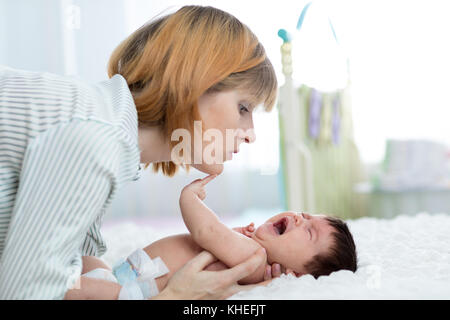 Mother comforts her crying newborn baby at home - Stock Photo