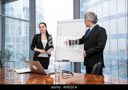 Young business woman and mature man making a presentati - Stock Photo