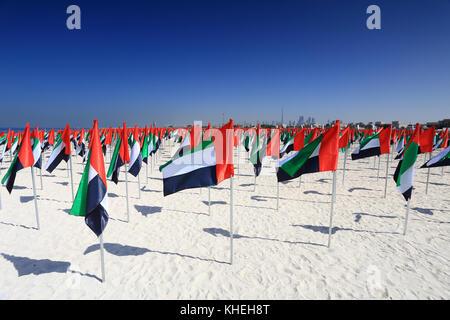 Flags of United Arab Emirates on beach. National holiday UAE flag day. - Stock Photo