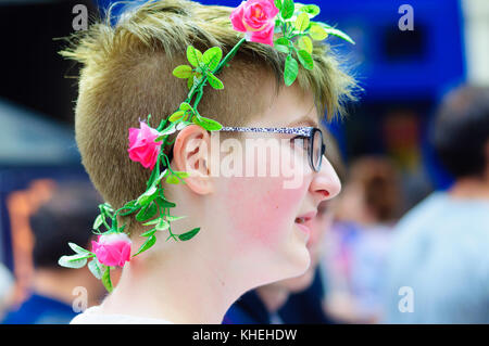 Female performer wearing glasses and a garland of flowers in her hair on the Royal Mile during the Edinburgh International - Stock Photo