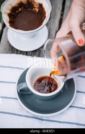 Delicious freshly brewed pour over coffee pouring into porcelain coffee cup - Stock Photo