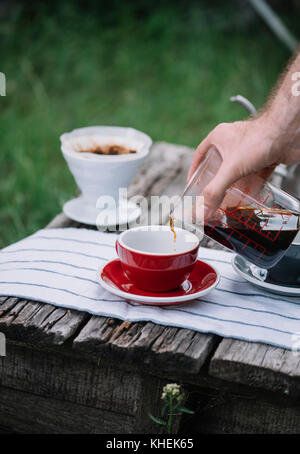 Delicious freshly brewed outdoor pour over coffee pouring into porcelain red coffee cup - Stock Photo