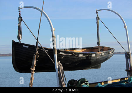 Black painted wooden lifeboat on davits. Background of river with bank in the distance and hazy blue sky. - Stock Photo