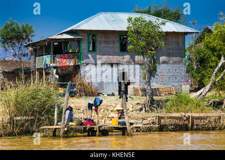 Inle Lake, Myanmar - March 4, 2017 : Two burmese women washing laundry by hand in a canal at the Inle Lake on March - Stock Photo