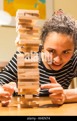 Young woman plays Jenga, stacking a tower with wooden blocks, concentrated - Stock Photo