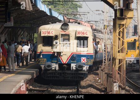 Commuter train and passengers at Vile Parle station on the Mumbai Suburban Railway network - Stock Photo