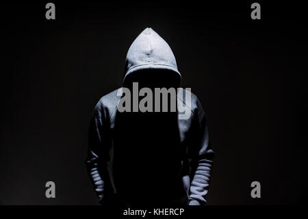Silhouette of man in the hood, dark mysterious man hoodie, murderer, hacker, anonymus on the black background with - Stock Photo