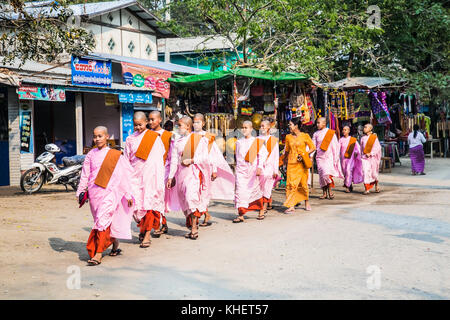 MINGUN, MYANMAR, MARCH 6, 2017: Buddhist nuns are walking at the streets of Mingun on March 6, 2017 in Myanmar. - Stock Photo