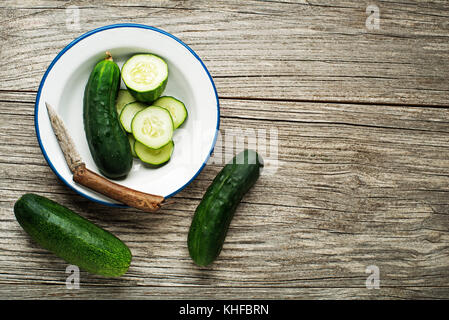 Fresh green cucumber sliced prepare for meal on wooden background - Stock Photo
