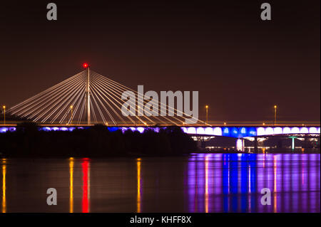 Night panorama of Swietokrzyski bridge over Vistula river at the center of Warsaw, Poland - Stock Photo