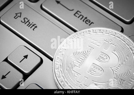 Silver bitcoint laying on keyboard near enter button - Stock Photo