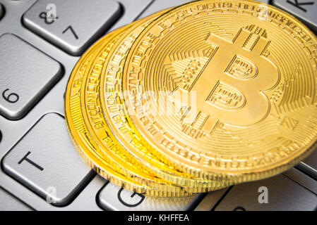 Stack of bitcoins on computer keyboard - Stock Photo