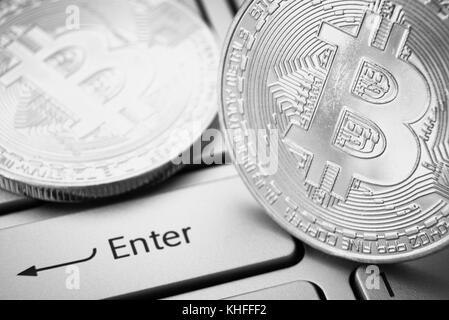 Bitcoins on laptop keyboard near enter button. Black and white photo - Stock Photo