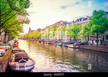 Channel in Amsterdam Netherlands at rays of sunset. Typical Amsterdam houses. Amstel river. Spring cityscape view - Stock Photo