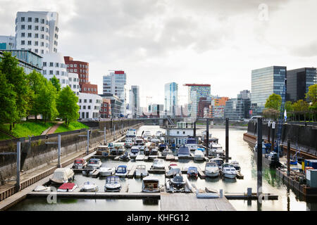 Cloudy day in Dusseldorf's harbour. Cityscape view on Medienhafen full of boats - Stock Photo