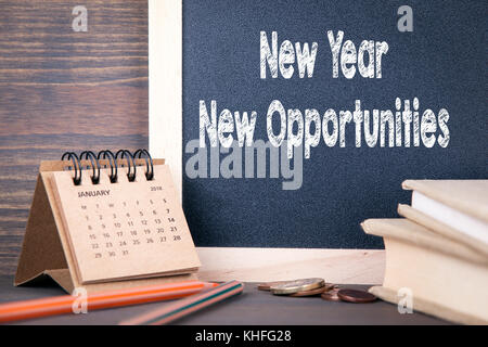 new year new opportunities. paper calendar and chalkboard on a wooden table - Stock Photo