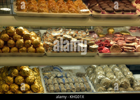 tasty and tempting biscuits, cakes and confectionery for sale on display in a greek bakers shop on the island of - Stock Photo