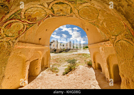 Rock cut church and its frescos with a view over the volcanic formations in the background, in Cappadocia, Turkey. - Stock Photo