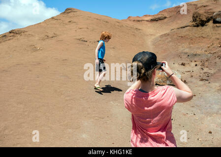 Girl taking picture of a boy in a park - Stock Photo