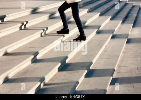 One teenage girl going up the stairs in motion blur and shadows of people following , on huge public outdoor stairway - Stock Photo