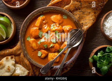 A bowl of delicious indian butter chicken curry with naan bread, basmati rice, and cilantro garnish. - Stock Photo