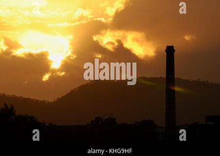 An other worldly gothic scene at sunrise where a hierarchy with sun/universe dominating a retired smoke stack, which - Stock Photo