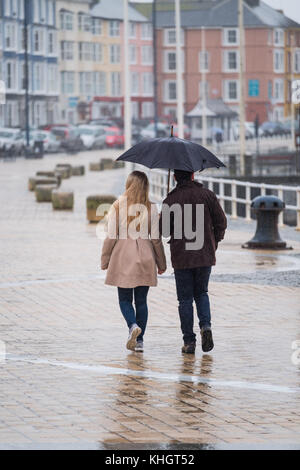 Aberystwyth  Wales UK, Saturday 18 Novemberr 2017  UK Weather: A couple  sheltering under their shared umbrella - Stock Photo