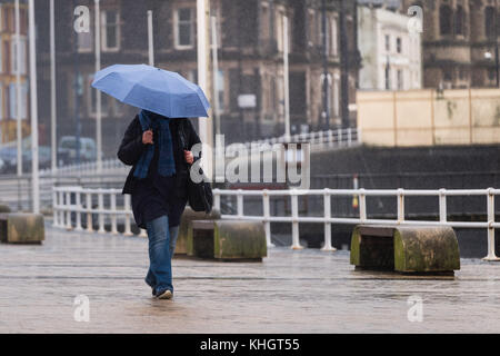 Aberystwyth  Wales UK, Saturday 18 Novemberr 2017  UK Weather: People walking under their umbrellas on the promenade - Stock Photo