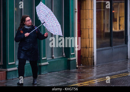Aberystwyth  Wales UK, Saturday 18 Novemberr 2017  UK Weather A woman struggling with her umbrella on a grey, overcast, - Stock Photo