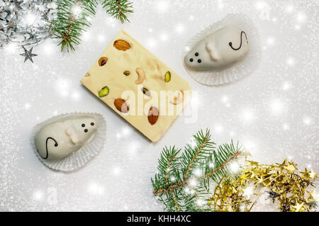 Two cakes in the form of white mice and a marzipan-and-cheese Turkish delight lying on the green branches of a Christmas - Stock Photo