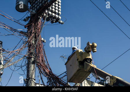 A confused electrician tries to do his job. Pole with lots of wires. - Stock Photo