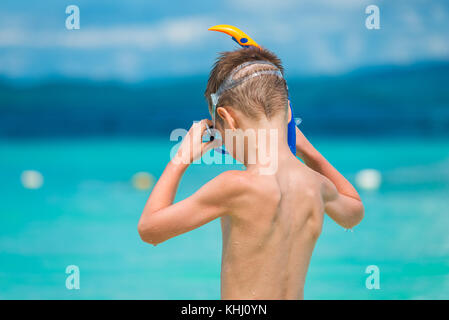 child wears a snorkeling mask on the seashore in the tropics - Stock Photo