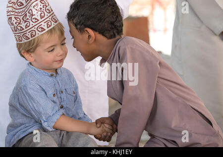 Nizwa, Oman, 10th Nobember 2017: omani kid and european kid giving eachother an eskimo kiss - Stock Photo