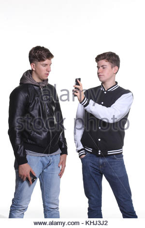 portrait on white background of two teenagers males using smartphone - Stock Photo